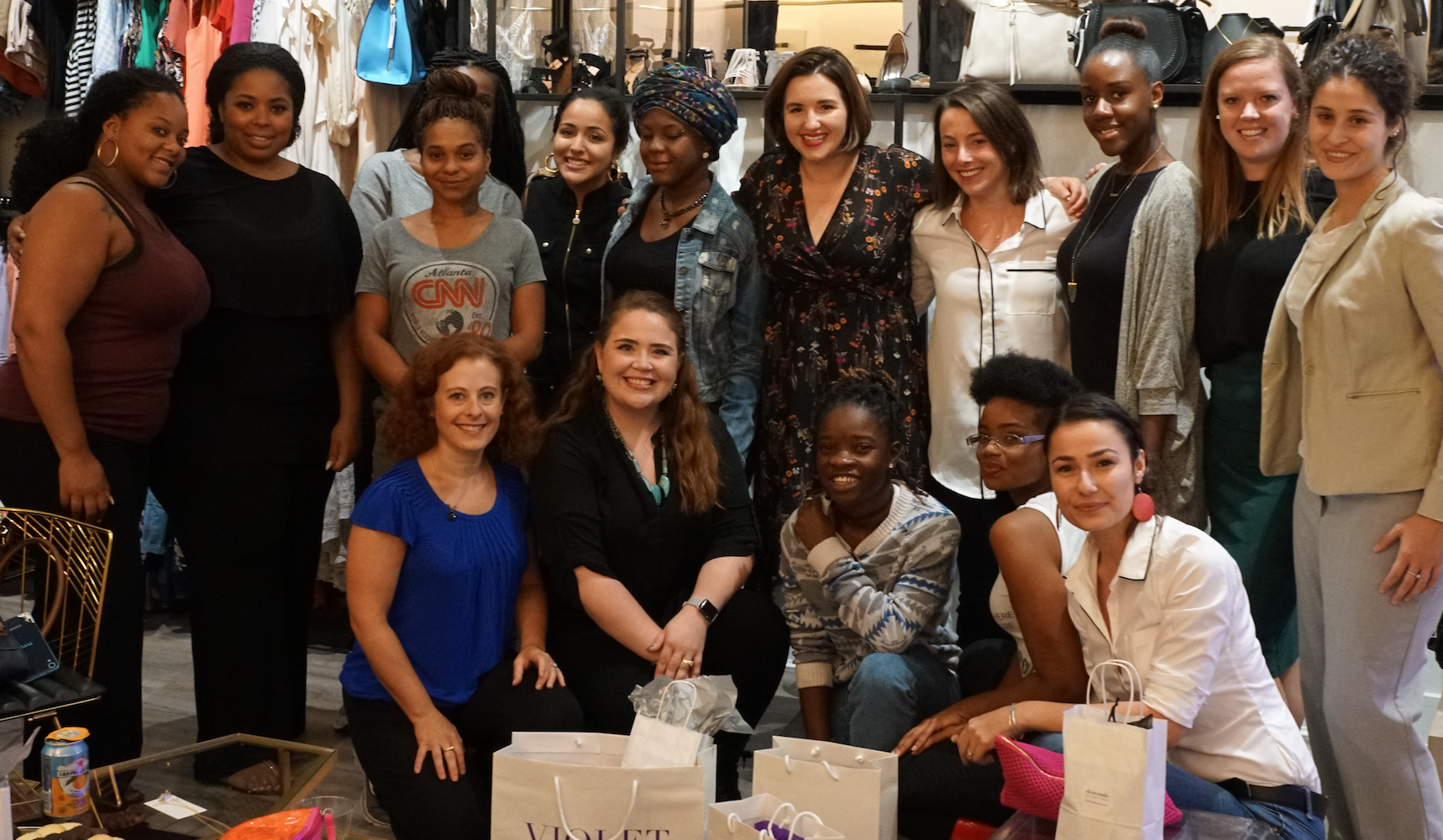 Women stand together after makeover experience in a boutique clothing store.